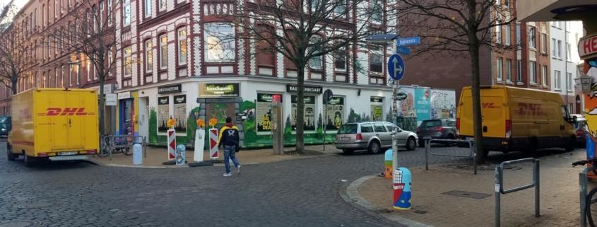 Straßenkreuzung mit zwei parkenden DHL-Lieferwagen, Paketbote in der Mitte § Foto: Tabea Philipp