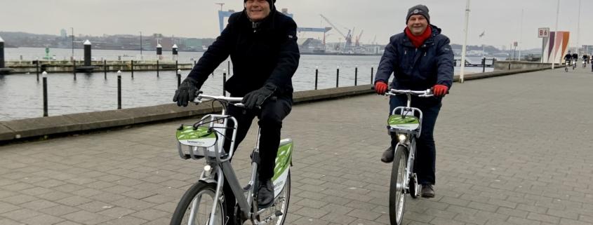 """Rolf Mützenich und Mathias Stein fahren mit einem """"Sprottenflotten""""-Fahrrad an der Kiellinie entlang § Foto: Jonas Beck"""