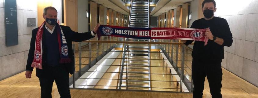 Mathias Stein und Lars Klingbeil halten einen Fanschal, auf dem Holstein Kiel und FC Bayern München steht
