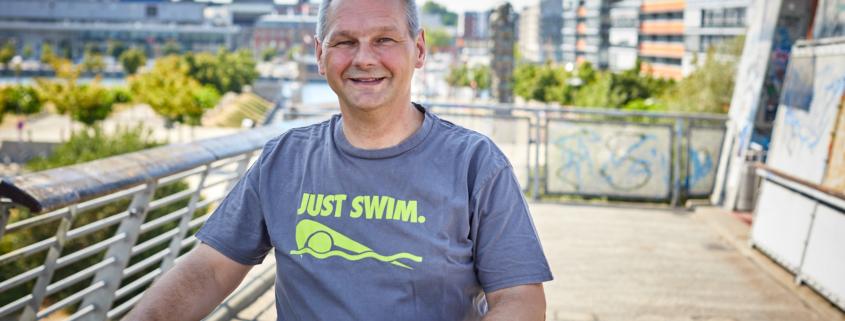 """Mathias Stein mit einem T-Shirt auf dem """"Just swim"""" steht mit einem Fahrrad auf der Gaardener Brücke § Foto: Olaf Bathke"""