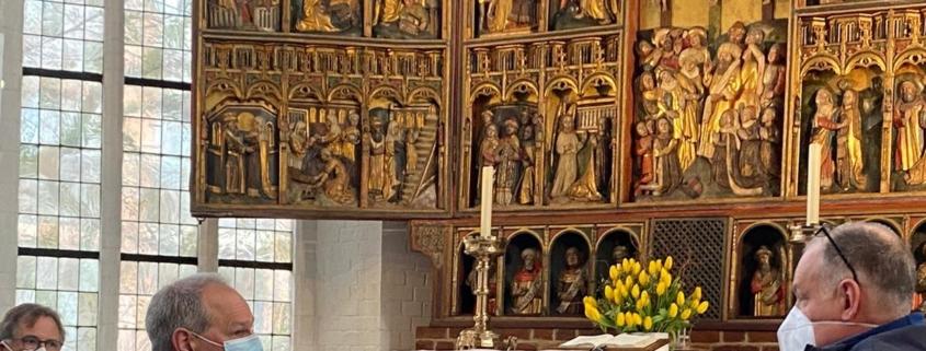 Mathias Stein mit zwei weiteren Personen vor dem Altar in der Kirche St. Nikolai § Foto: Amira Amri