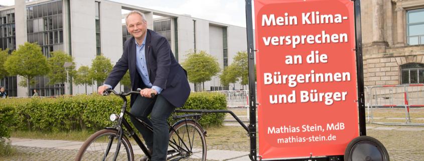 """Mathias Stein auf dem Fahrrad vor dem Bundestag, das Rad hat einen Anhänger auf dem steht """"Mein Klimaversprechen an die Bürgerinnen und Bürger"""""""