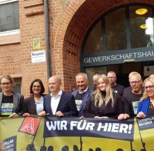 """Olaf Scholz und Mathias Stein mit weiteren Menschen hinter einem Banner der IG Metall, auf dem steht """"Wir für Hier"""" vor dem Kieler Gewerkschaftshaus § Foto: Tabea Philipp"""